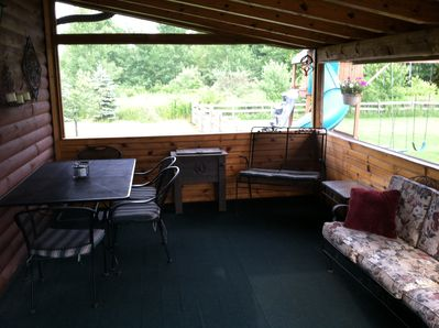 Rear covered porch that is also screene in and carpeted.