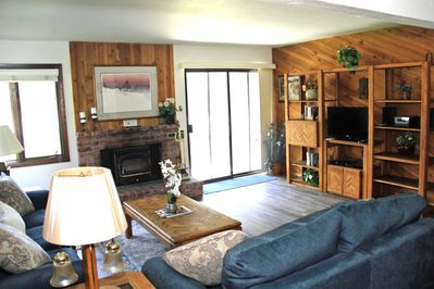Mammoth Lakes Condo Rental Wildflower 45 - LR Features a Woodstove and Flat Screen TV. Access to outside deck.