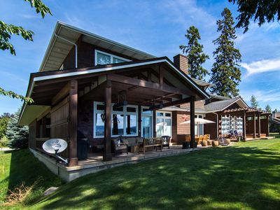 Back of home facing lake with three patios, bbq, fire pit, spa.