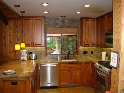 The updated kitchen has granite countertops and heated stone floors