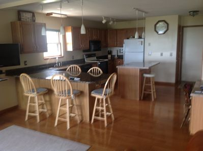Fully stocked kitchen with granite counter tops and extra seating