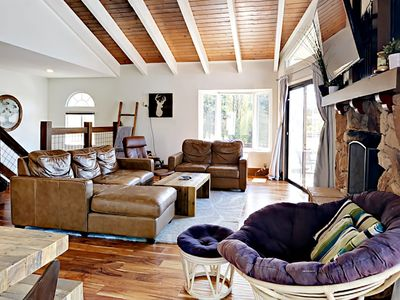 """Living Room - The sunlit living space is furnished with comfy leather furniture and a 65"""" TV."""