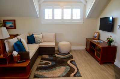 Living room with vaulted ceilings, a/c, tv and free wifi