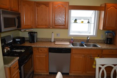 Kitchen with Gas Stove, Microwave, Dishwasher, Refrigerator.