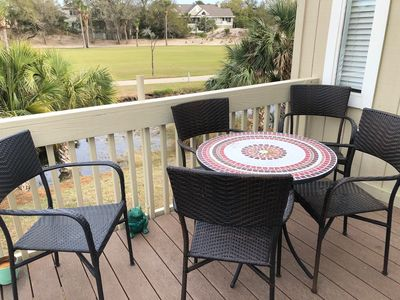 The front porch has a table set to enjoy the view wildlife in the lagoon and the golf course.