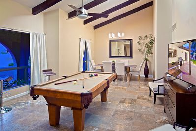 Open game room with fun pool table, large TV, and high ceilings