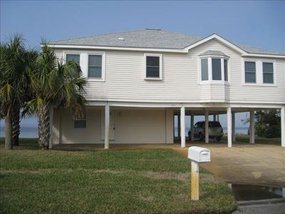 Front of house with lots of parking, nice front yard and water behind.