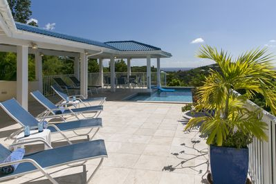 2000 sq ft white travertine deck with lounge chairs, tables & shaded pool gazebo