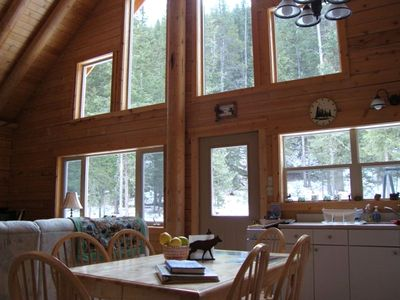 View of living/dining room windows which look out onto an acre of wooded land