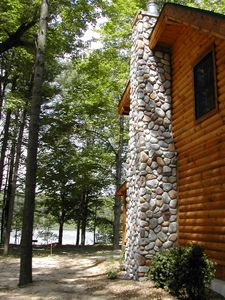 Side of cabin with stone chimney