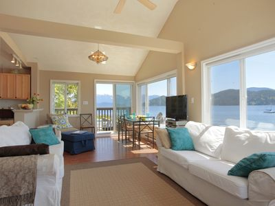 Living and dining areas offer panoramic views of Gibsons Harbour and mountains.