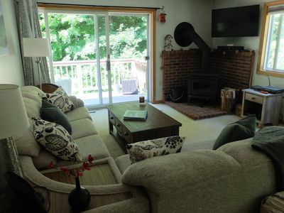 Living area with L-shaped couch and easy chair, flat screen TV, and wood stove.