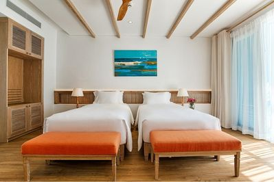 A bedroom area with twin single beds and plush pillows.