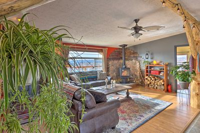 The cozy space features hanging plants & lights around a wood-burning stove.