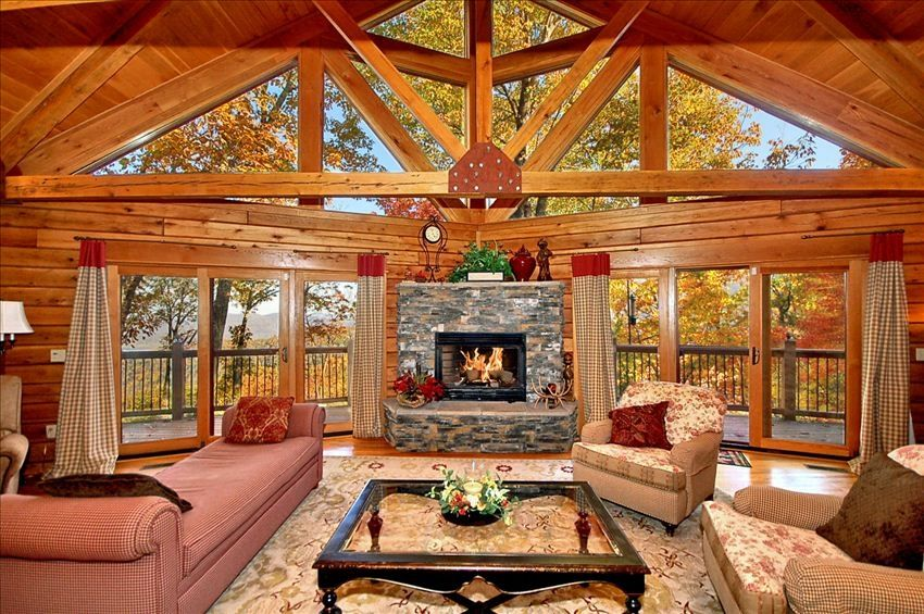 Great Room With Stone Fireplace And Wraparound Deck Upscale Furnishings