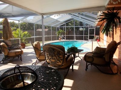 Screened in Pool cage, with privacy fence outside. BBQ area and fire pit.