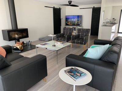 """Black01 living area with lime washed timber floors, European fire and 65"""" HD TV."""
