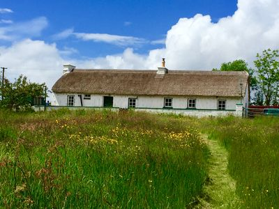 Photo for Traditional thatched cottage near the sea: log burner, paddock and bikes