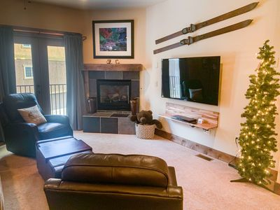 Cozy living room with two leather, swivel recliner chairs, and a pull out couch.