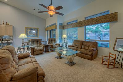 Large windows in cozy family room provide view of backyard with exciting amenities