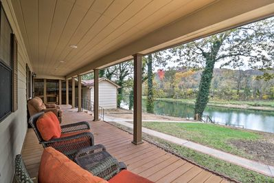 The waterfront vacation rental home boasts a dock & furnished, covered porch.