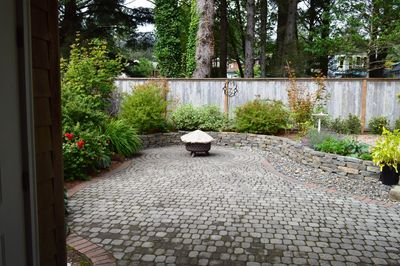Large fully fenced back stone patio with gas BBQ, two tables with ample patio chairs and a fire pit