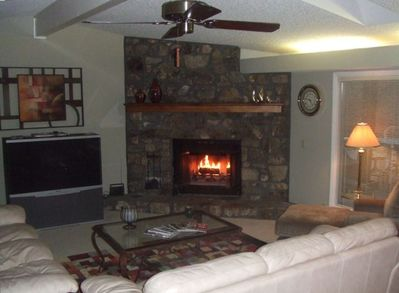 Living area with comfortable seating, stone fireplace, and big screen TV.
