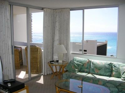 The living room opening onto the balcony, ocean all the way to the horizon