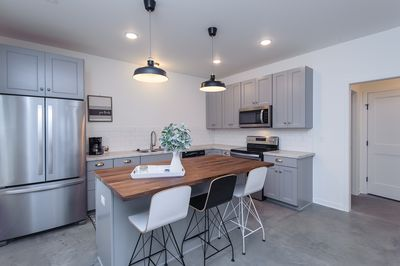 Large kitchen with brand new stainless steel appliances.