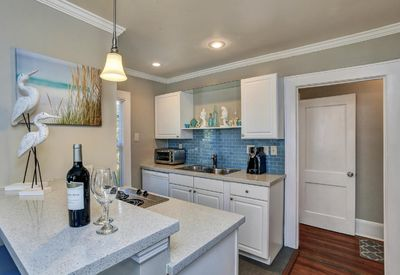 Open plan kitchen w/quartz tops and beautiful glass tile backsplash