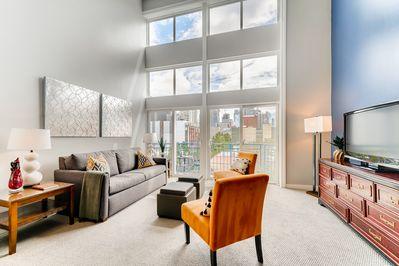 Living room gets plenty of natural sun with wide loft style windows