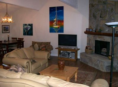 Open Great Room with 15' vaulted ceilings, oil on canvas art, rock fireplace