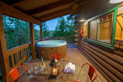 Hot tub on covered wrap around deck with mountain views