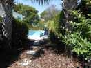 Fenced pool and patio area with garden/ lounges/chairs/tables/natural gas grill