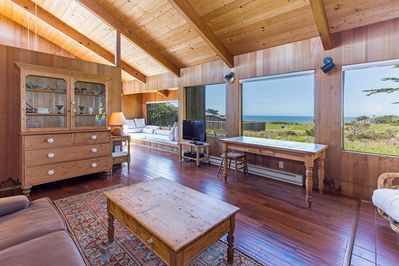 Rustic living room with large windows and ocean view