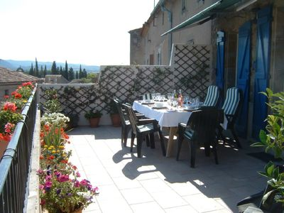 Outside terrace with dining table and sun chairs