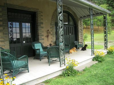 Front porch overlooking the walled garden, mountains & stable house.