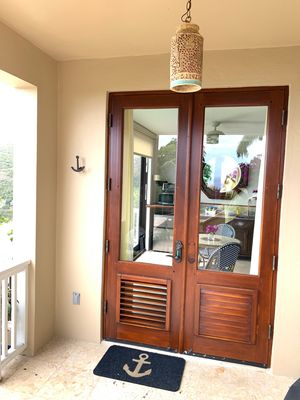 Private entry with custom mahogany french doors handmade Schnell pottery light.