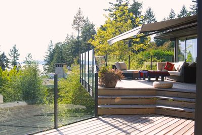 Sun drenched deck with sectional sofa, and BBQ with partial views of ocean