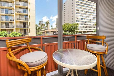 Lanai with white patio table and two rattan bar stools