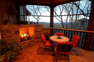 Spacious screen porch with gas fireplace at dusk.