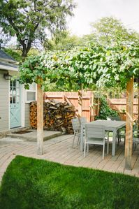 Backyard features outdoor dining area for six, grill and pergola with grapevines