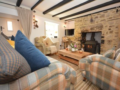 Delightful lounge with cosy sofa and a warming wood burner