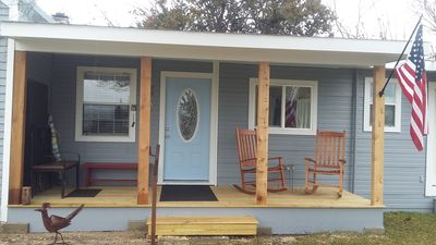 New porch with rocking chairs overlooking large side yard.