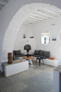 The living room from the kitchen, the stone arch and its traditional fireplace
