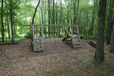 Relax on the porch while you watch your children play on this wooden playground.