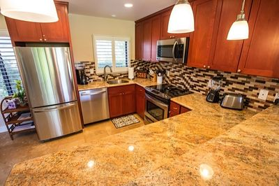 Beautiful kitchen with granite counters and full size stainless appliances.