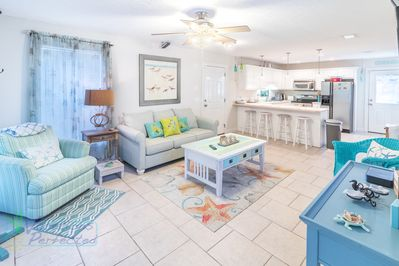 View of the fun sea colored relaxing living room and kitchen in the background, ocean wonderland inspired decorations