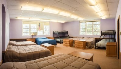 Bunk room with 8 queen beds and 5 twin beds