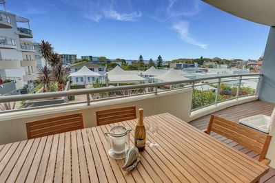 Large balcony with timber dining setting and great views.